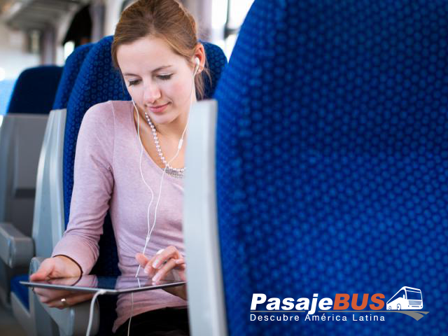 Mujer viajando en bus y usando su ipad. Disfruta en viajes largos